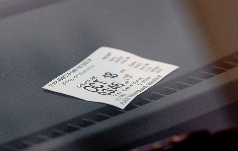 A parking receipt from one of the city's new parking kiosks sits on the dasboard of a car parked on Free Street Friday afternoon.