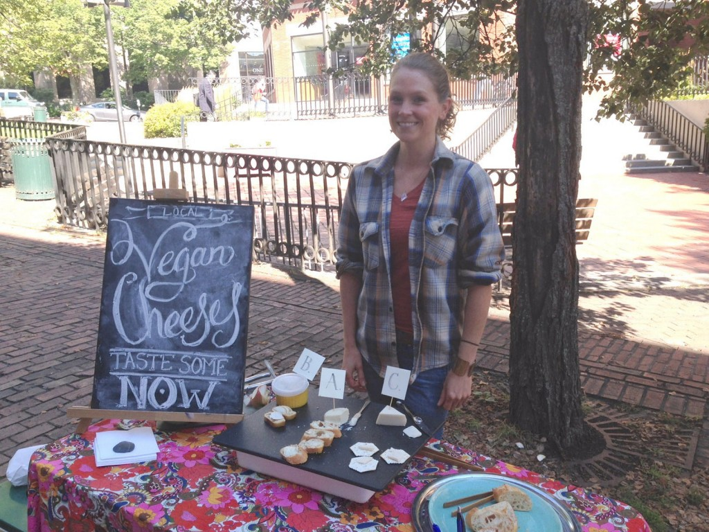 Betsy Nelson offers a taste test of her vegan fermented nut cheeses during a recent farmers market in Portland. She is working with students of Boston College's Carroll School of Management to create a business plan to market her cheeses.