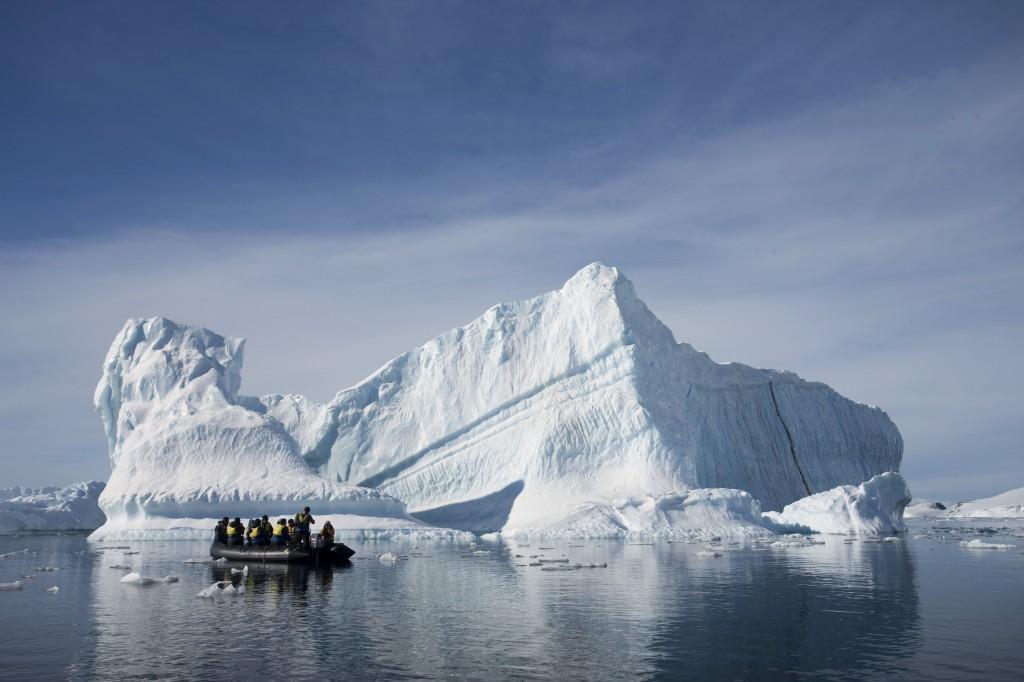 AP An inflatable boat carries tourists past an iceberg along the Antarctic Peninsula.