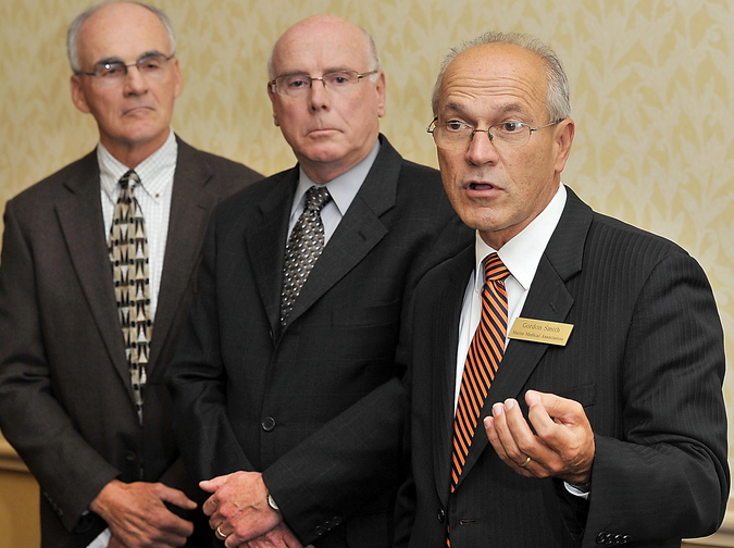 Gordon Chibroski, Staff Photographer. Gordon Smith, right, executive vice president of the Maine Medical Association, answers questions from the media Saturday as, (from left), Dr. Guy Raymond, incoming president of Maine Medical Association and Neal Lane, AARP National Policy Council member, look on. He made his comments during a press conference on the negative aspects of Maine's failure to accept federal dollars for expanding Medicaid.