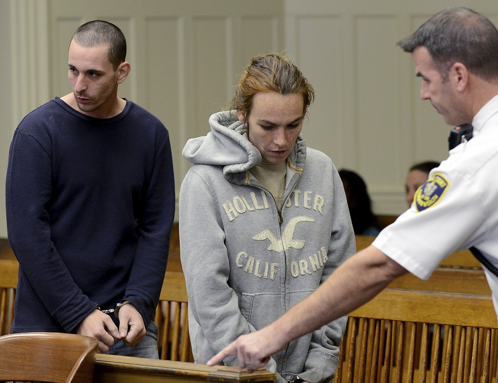 Ryan Barry and Ashley Cyr are led into Brockton, Mass., Superior Court for arraignment Friday on charges of manslaughter in the death of their 5-month-old daughter Mya Barry, by giving her a bottle of formula with heroin in September 2011. They pleaded not guilty.