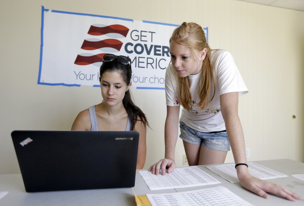 Ashley Hentze, left, of Lakeland, Fla., gets help signing up for health care from Kristen Nash, a volunteer with Enroll America, a private, non-profit organization running a grassroots campaign to encourage people to sign up for health care, Tuesday, Oct. 1, 2013. On the day consumers start perusing newly launched federal online health exchanges, Republican governors who oppose President Barack Obama's insurance overhaul are mostly sitting on their hands. But the law is going into effect without them.