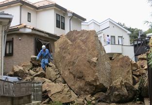 A firefighter walks over debris in Kamakura, Japan, after a powerful typhoon hit the metropolitan area Wednesday.