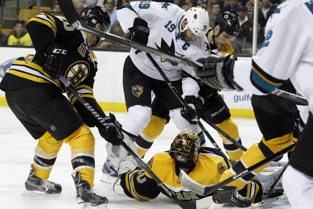 Tuukka Rask of the Boston Bruins makes a save while lying on his back Thursday night as Joe Thornton of the San Jose Sharks attempts to get a stick on the puck in the first period of the Bruins' 2-1 victory.