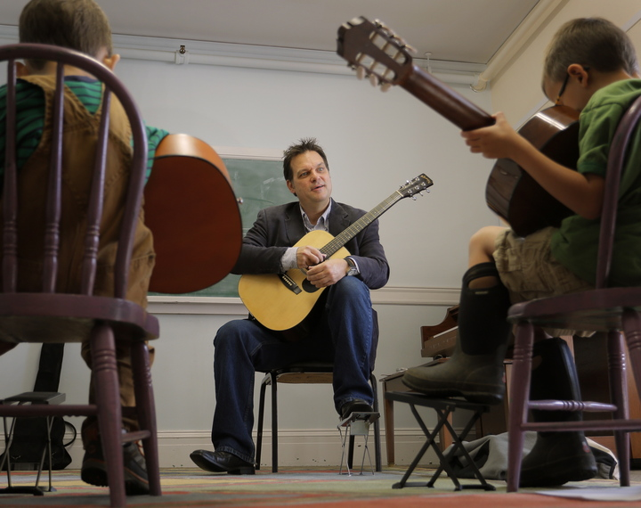 Don Pride teaches a guitar to Oliver Newton, 5, left, and Michael Madden, also 5, in a class for home-schooled students at the Portland Conservatory of Music on Tuesday.