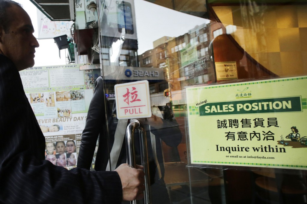 """A customer enters a Chinese bakery that has a sign posted in the door, """"Hiring! Sales Position Inquire within,"""" Tuesday in New York. The U.S. economy added just 148,000 jobs in September, suggesting that employers held back on hiring before a 16-day partial government shutdown began Oct. 1. Still, hiring last month was enough to lower the unemployment rate."""