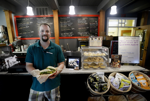"""Mark Claussen of Saco Island Deli in Saco shows off a """"Mainah,"""" one of the deli's specialty sandwiches."""