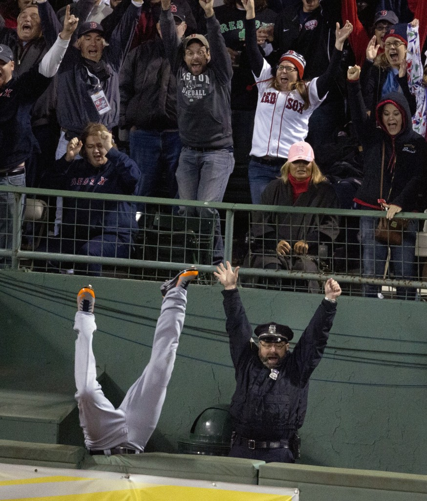 Boston police officer Steve Horgan celebrates as Tigers right fielder Torii Hunter flips over the fence into the bullpen while trying to catch David Ortiz's grand slam Sunday night.