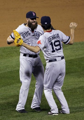 Boston Red Sox relief pitcher Koji Uehara celebrates with teammate Mike Napoli after getting St. Louis Cardinals' Matt Holliday to fly out and end Game 5 of baseball's World Series Monday, Oct. 28, 2013, in St. Louis. The Red Sox won 3-1 to take a 3-2 lead in the series.