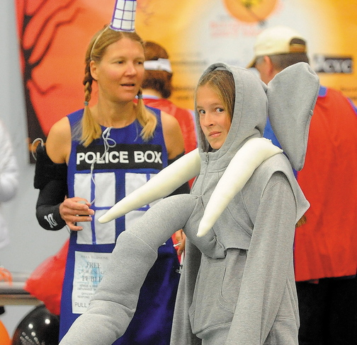 Alison Stabins, 11, center, dressed as an elephant, and her mother, Amy, dressed as Tardis from Dr. Who, wait for the start of the Freaky 5K Fun Run organized by Hardy Girls Healthy Women on Saturday at Colby College.
