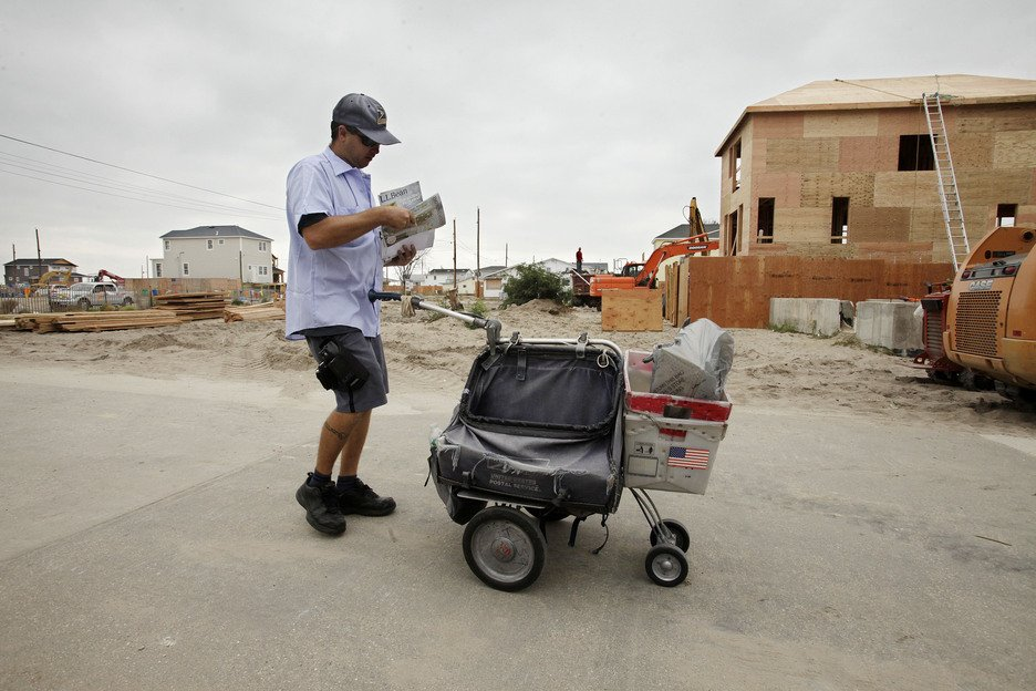 A postal worker makes his rounds through Breezy Point in the Queens borough of New York on Oct. 17. A year ago on Oct. 29 flooding and a fire swept through the neighborhood, leveling more than 100 homes. The house on the right is one of the few homes that burned to the ground that is now under reconstruction.