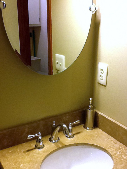 Attaching a dent puller to each of the upper corners of a mirror glued to the wall allowed easy removal with minor patchable damage to the wall and options for a new mirror.