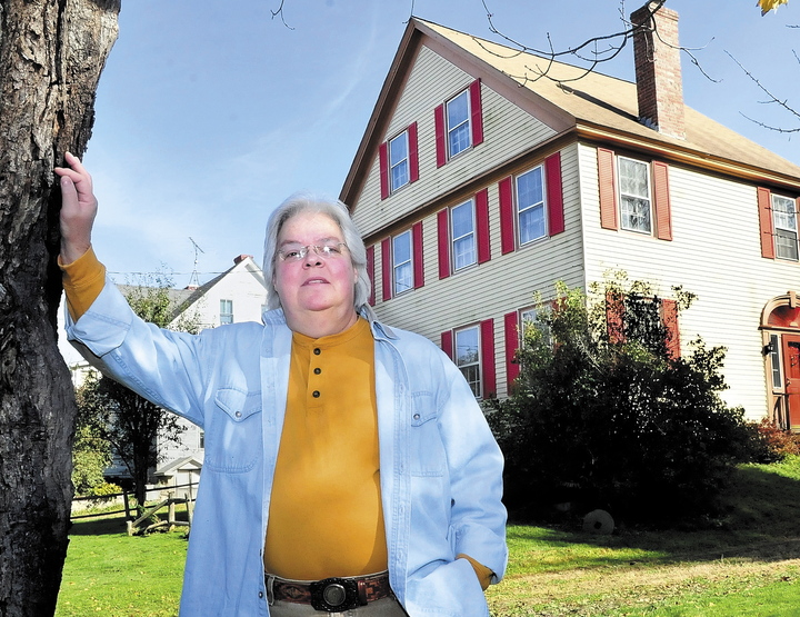 """Marty Golias, originally from Salem, Mass., stands in front of her home on the Falls Road in Benton where she has lived for 13 years. She believes that the house, which is described as haunted in Tom Verde's book """"Maine Ghosts and Legends,"""" is home to friendly spirits."""