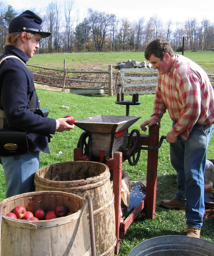 A visitor tries his hand at making cider as a period re-enactor looks on at the Washburn-Norlands Living History Center in Livermore. The center invites the public to step back in time at its fall festival on Saturday to see how it interprets farming in the 1870s, while raising funds for the rebuilding of its historic barn, destroyed by fire in 2008.