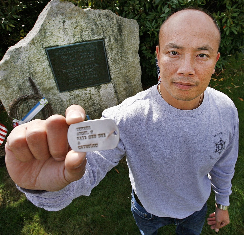 Peter Nguyen of Plymouth, Mass., holds a military dog tag bearing the name of Angel Torres. Nguyen, who lost his father in the Vietnam War, says he will fly anywhere to give the tag to its owner or to relatives of the owner. Clues on the tag suggest that Torres may have been from New England.
