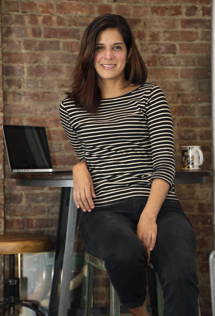 Mishelle Farer poses for picture in her apartment, where she rents a room on Airbnb, in New York, Thursday, Oct. 10, 2013. Farer is an avid user of Airbnb, a website that allows travelers to rent other people's homes or rooms. (AP Photo/Seth Wenig)