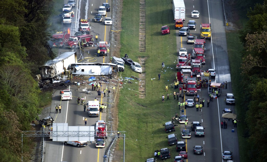 Emergency personnel search the scene near a collision involving a bus on I-40, in Dandridge, Tenn, on Wednesday.