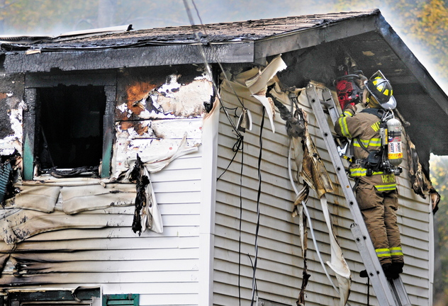 A firefighter cuts a hole to ventilate the attic of a home at 119 Granite Hill Road in Manchester on Saturday. The body of Sam Spinicci, 56, was found in a bedroom.