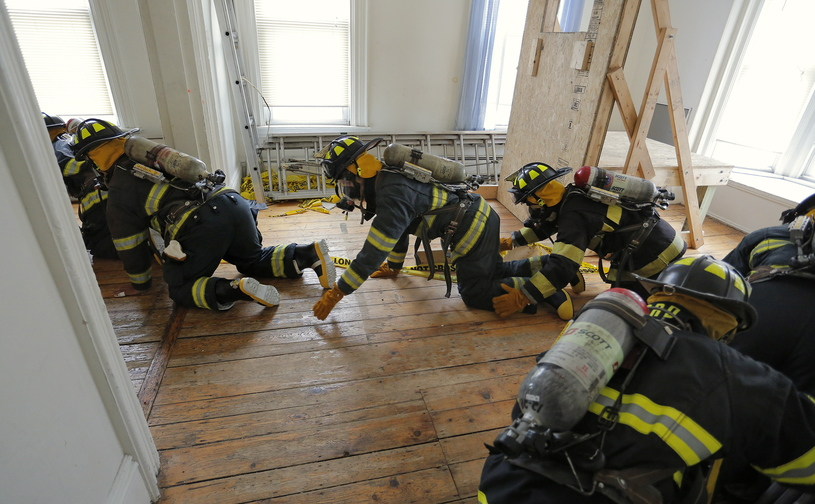Students from Portland and Deering high schools work their way through a vacant building at 65 Elm St. in Portland on Saturday as part of their yearlong Introduction and Orientation to Fire Service course.