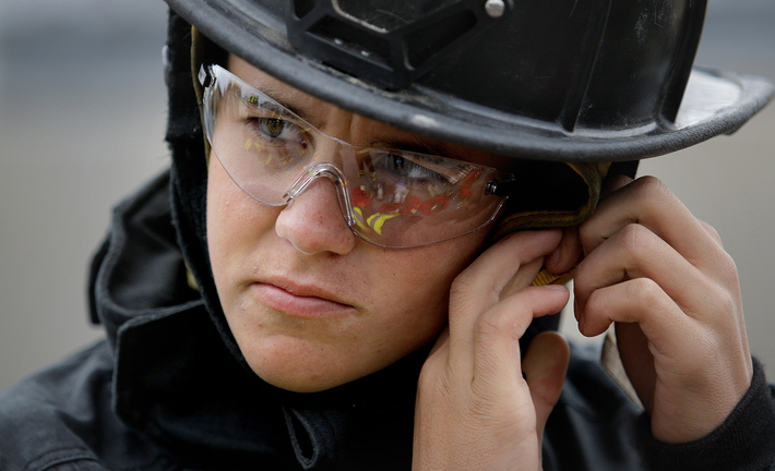Silas Corman, 17, a Portland High senior, adjusts his firefighting helmet before entering a building on Elm Street in Portland with other students from Portland and Deering high schools on Saturday. The exercise was part of a course offered by the schools in conjunction with the Portland Fire Department.