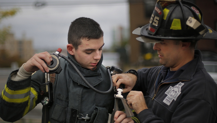 Owen Sprague, 15, a Deering High sophomore, gets some help with his regulator from Portland firefighter Wendell Howard on Saturday during the class.