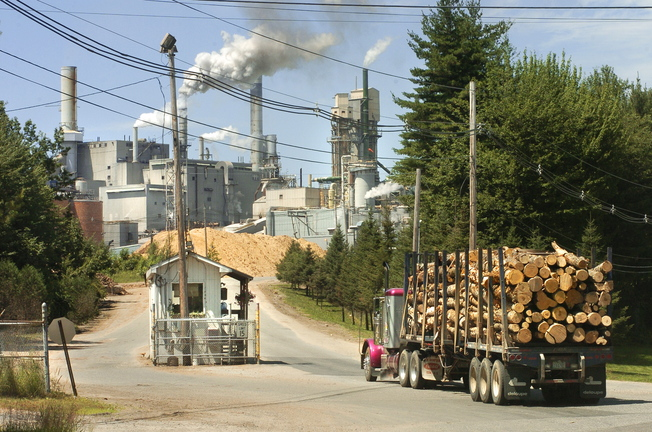 A truck loaded with logs enters a paper mill in Jay in 2005. The paper industry backs Maine's proposal to ease anti-smog rules, saying it will remove a barrier to major investments in mills. Wood pellet manufacturers also have expressed support.