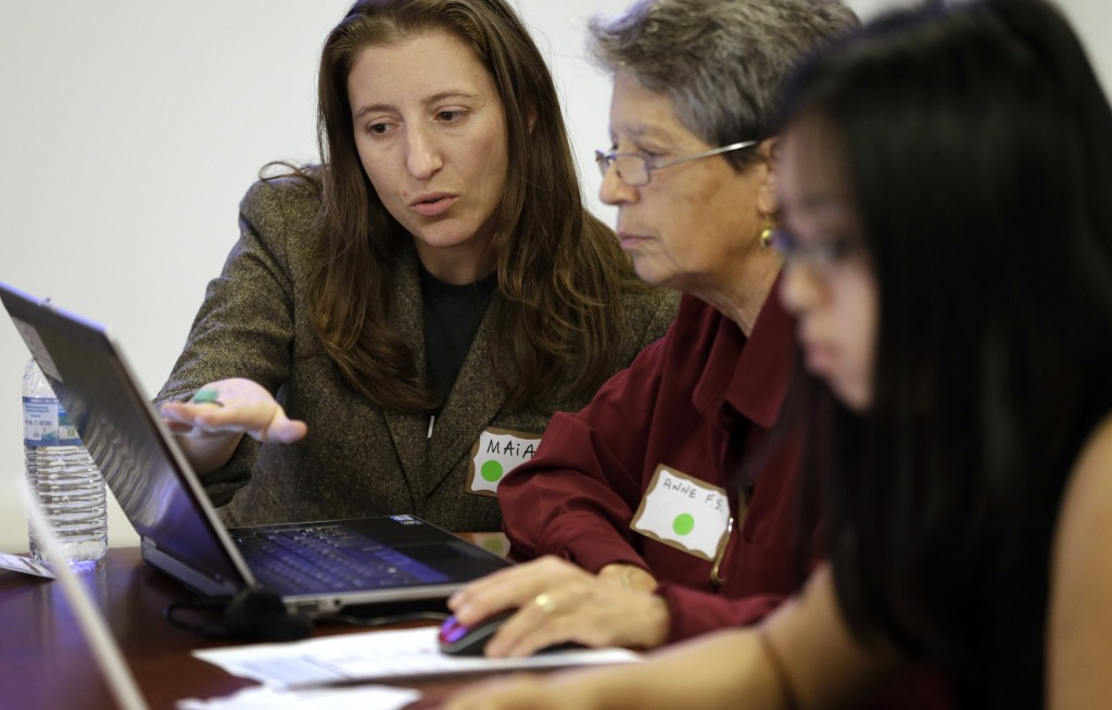 "Maia Weinstock, left, of Cambridge, Mass., a Brown University graduate, works with Anne Fausto-Sterling, of Cranston, R.I., center, a professor of biology and gender studies, during a Wikipedia ""edit-a-thon,"" on the Brown campus, in Providence, R.I."