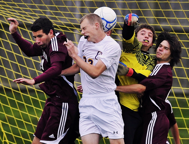 Brady Levesque of Cheverus gets a ball in the back of the head Tuesday as Cheverus keeper Charlie Mull punches away a corner kick during a 1-0 loss to Gorham. In front for Gorham are Matt Hooker, left, and Jon Gray.