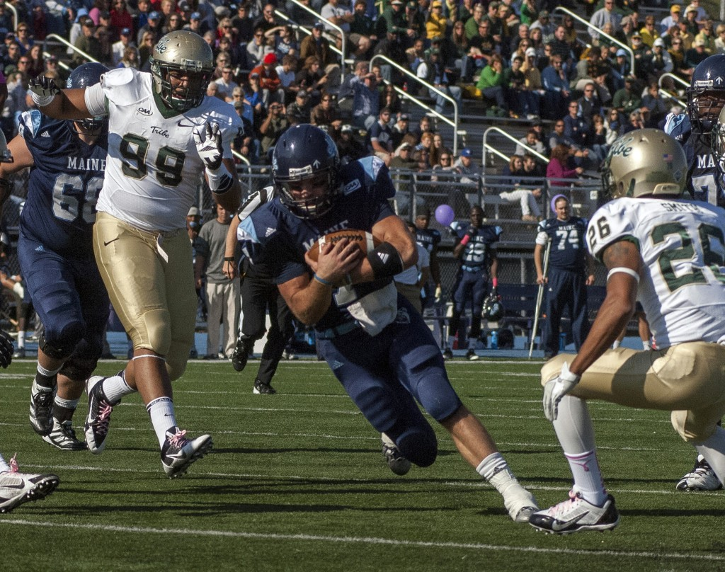 Maine quarterback Marcus Wasilewski carries the ball inside the 5-yard line past William & Mary players Tyler Clayter (99) and Ryan Smith (26) converge.