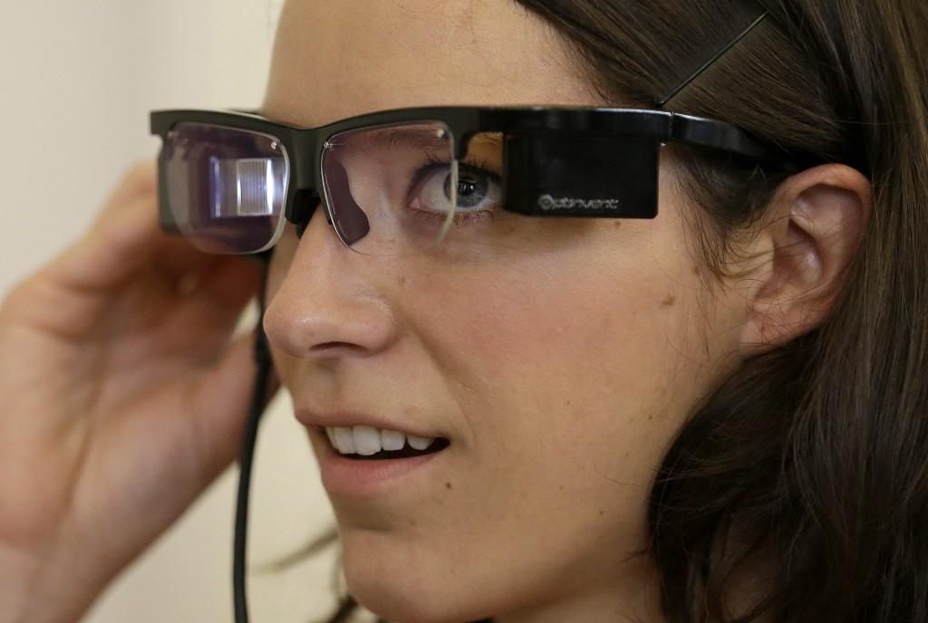Claire Collins checks Optinvent ORA-S augmented reality glasses at a conference for the business of wearable technology in San Francisco on Monday.