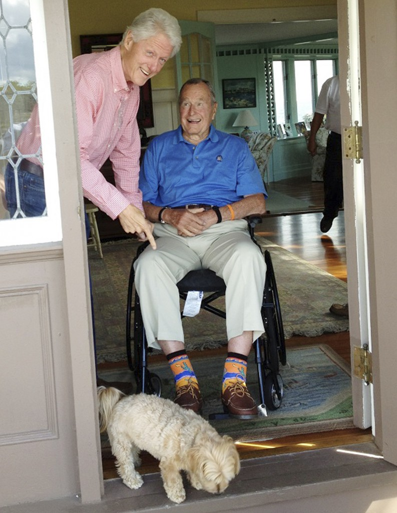 Former President Bill Clinton points to western-themed socks worn by former President George H.W. Bush at Bush's home in Kennebunkport during a visit last month. Bush has donated the socks, an autographed picture of the moment and a signed letter of authenticity to a charity auction for the Roman Catholic Diocese of Portland.