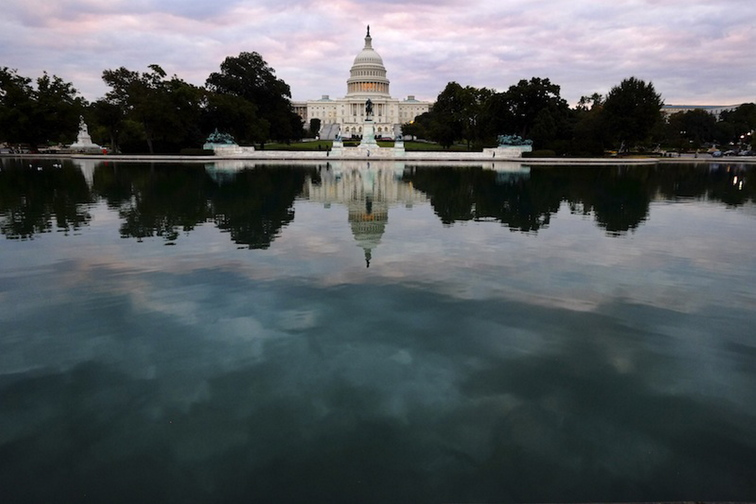 The Capital is mirrored in the Capital Reflecting Pool on Capitol Hill in Washington early Tuesday, Oct. 1, 2013. Congress plunged the nation into a partial government shutdown Tuesday as a long-running dispute over President Barack Obama's health care law stalled a temporary funding bill, forcing about 800,000 federal workers off the job and suspending most non-essential federal programs and services.