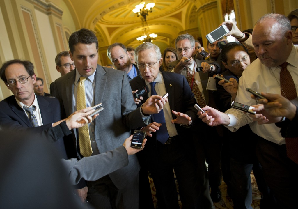 """Senate Majority Leader Sen. Harry Reid, D-Nev., is surrounded by reporters after leaving the office of Senate Minority Leader Sen. Mitch McConnell, R-Ken., on Capitol Hill on Monday in Washington. """"We're getting closer,"""" Reid told reporters."""