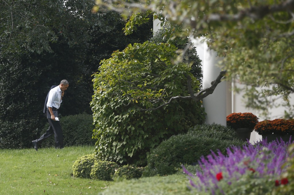 """President Barack Obama walks back to the Oval Office after he visited Martha's Table, which assists the poor and where furloughed federal employees are volunteering, in Washington on Monday. Speaking there Obama said that if Republicans can't resolve the standoff over the debt ceiling and the partial government shutdown, """"we stand a good chance of defaulting."""""""