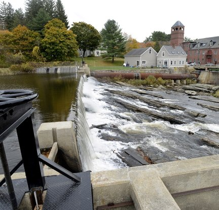 Water from the Royal River flows over the Bridge Street dam in Yarmouth. The dam is one of two dams the town is considering removing from the river.