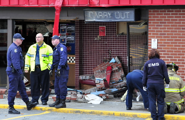Firefighters, state police and Skowhegan Police Chief Ted Blais, second from left, investigate the scene where a truck loaded with logs crashed into the Pizza Hut restaurant in Skowhegan, killing driver Michael Morin of Oakland.