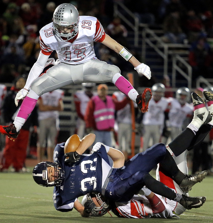 Justin Zukowski of Portland goes down as Hayden Owen of South Portland goes up Friday night during the Battle of the Bridge at Fitzpatrick Stadium. Zukowski rushed for 226 yards in a 38-14 victory.