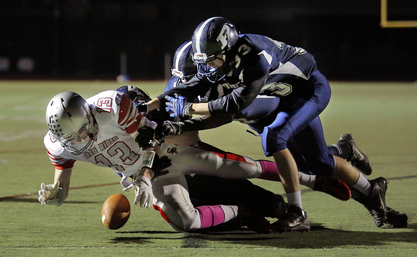 South Portland's Hayden Owen fumbles the ball at the goal line under pressure from Portland's defense including Domenic Fagone, at right, during first-half action at Fitzpatrick Stadium on Friday.