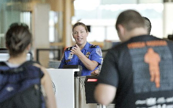 TSA employee Donna Castle calls travelers to the Jetport's document check-in site as they prepare to go through security last month. The TSA has added Portland to the list of airports offering expedited screening.