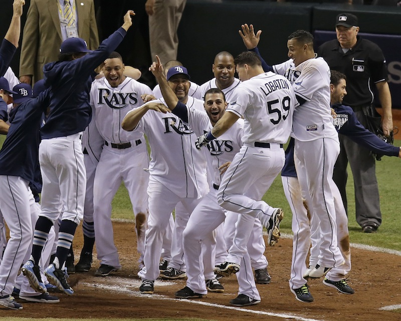 Tampa Bay Rays' Jose Lobaton (59) is surrounded by teammates as he heads to home plate after hitting a walk off home run in the ninth inning against the Boston Red Sox in Game 3 of an American League baseball division series in St. Petersburg, Fla., Monday, Oct. 7, 2013.Tampa Bay Rays won the game 5-4.