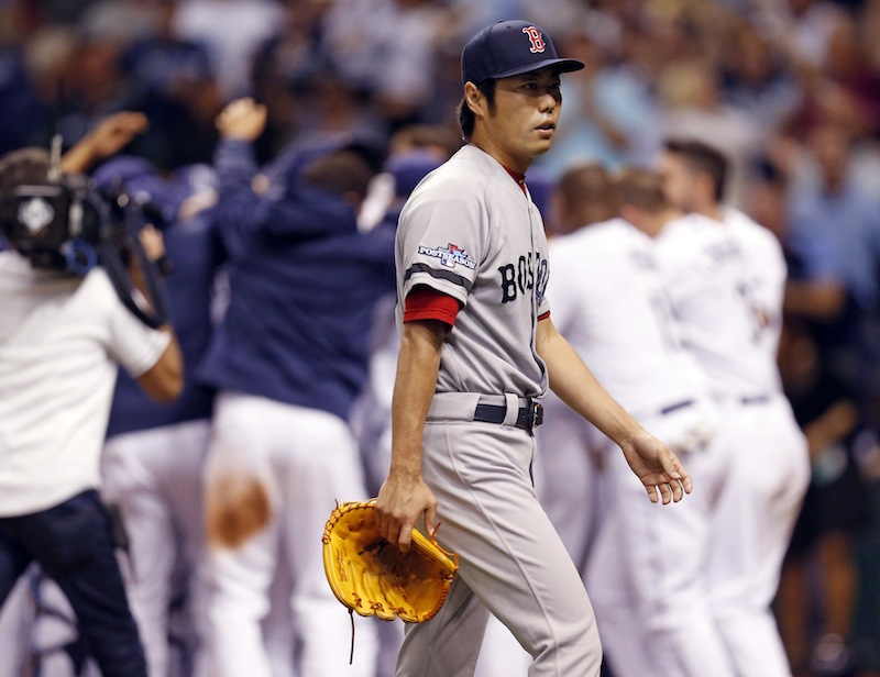Boston Red Sox's relief pitcher Koji Uehara walks away as the Tampa Bay Rays celebrate the game winning home run by Jose Lobaton in the ninth inning in Game 3 of an American League baseball division series, Monday, Oct. 7, 2013, in St. Petersburg, Fla. (AP Photo/Mike Carlson) Tropicana Field