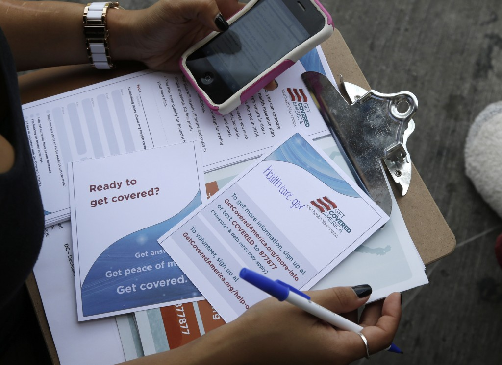 In this Wednesday, Sept. 25, 2013, photo, Maygan Rollins, 22, a field organizer with Enroll America, holds a clipboard with pamphlets while canvassing at a bus stop in Miami. Enroll America is a private, nonprofit organization running a grassroots campaign to encourage people to sign up for health care offered by the Affordable Care Act.