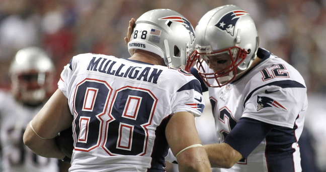 Patriots tight end Matt Mulligan celebrates with quarterback Tom Brady after scoring a touchdown in the first half Sunday night against the Atlanta Falcons.