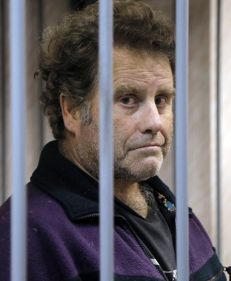The US captain of the Greenpeace ship 'Arctic Sunrise', Peter Willcox is kept behind bars in a court room in Murmansk, Russia, on Thursday, Sept. 26, 2013.