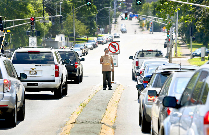 In this July 16, 2013 file photo, a man panhandles on a median on the corner of Marginal Way and Forest Avenue in Portland. Portland officers are using criminal trespass notices – and the threat of jail time – to keep chronic panhandlers off the medians.