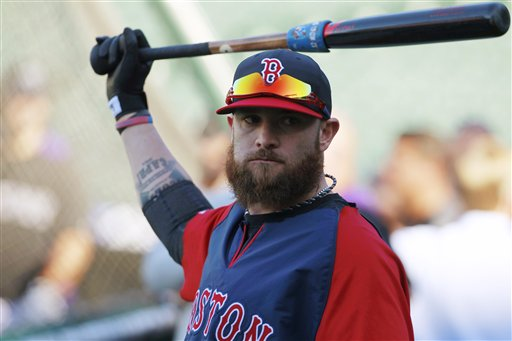 Boston Red Sox outfielder Johnny Gomes warms up before facing the Colorado Rockies in Denver on Sept. 25, 2013.