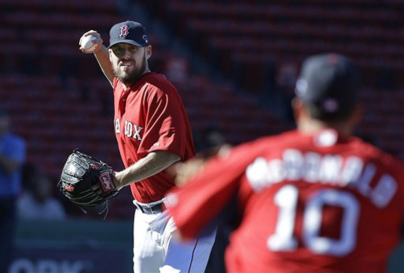 Boston Red Sox pitcher John Lackey winds up to throw to shortstop John McDonald (10) during a team workout at Fenway Park on Tuesday. The Red Sox host the Tampa Bay Rays in Game 1 of the AL divisional series on Friday.