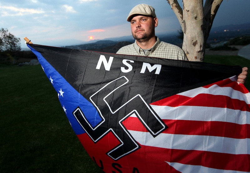 In this Oct. 22, 2010 file photo, Jeffrey Hall, who was killed by his then-10-year-old son, holds a neo-Nazi flag while standing at Sycamore Highlands Park near his home in Riverside, Calif. A California judge ruled Thursday, Oct. 31, 2013, that the boy, now 13, will spend at least the next seven years in a state juvenile facility. Judge Jean R. Leonard said the maximum the boy can serve would be until he is 23. He'll be eligible for parole in seven years. The decision came after prosecutors and defense attorneys argued for months about the best placement to assure his safety and rehabilitation.