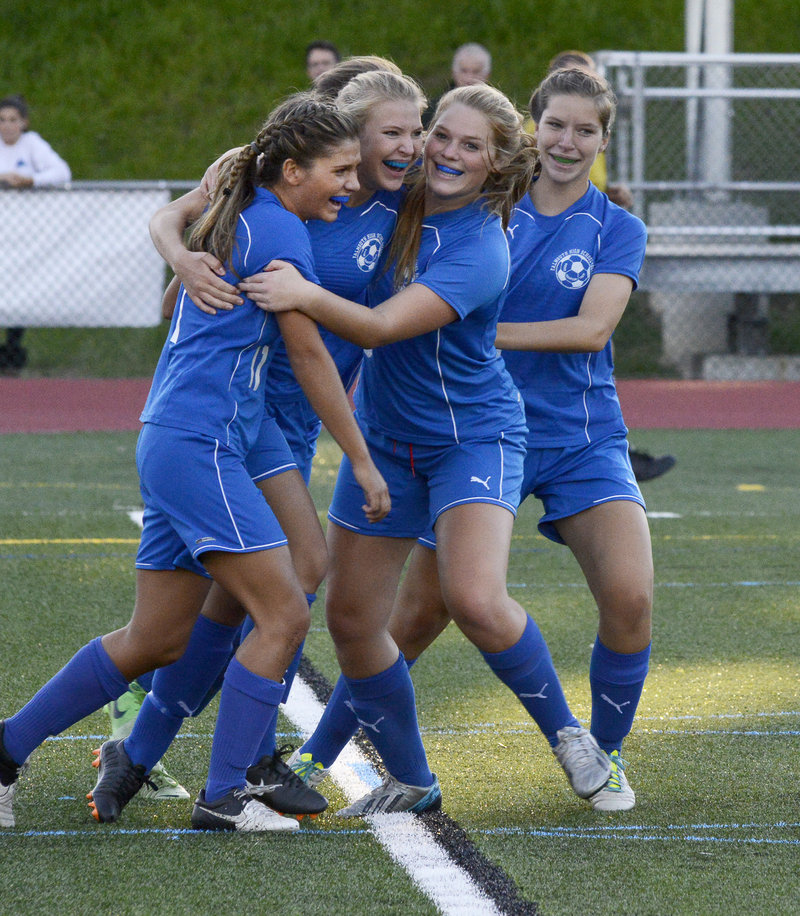 Taylor Russell, second from the left, gets congratuled by Mary Catherine Kowalsky, left, Laura Bauer and Brianna Russell after scoring in Monday's girls' soccer game against Yarmouth. Falmouth won, 3-1.