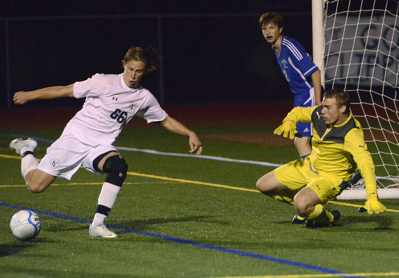 Yarmouth's Wyatt Jackson prepares to hit a shot as Falmouth keeper Will D'Agostino moves to keep it wide on Monday night.